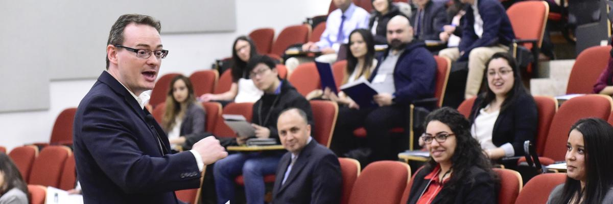 Middle age businessman talking to a group of students in a lecture hall