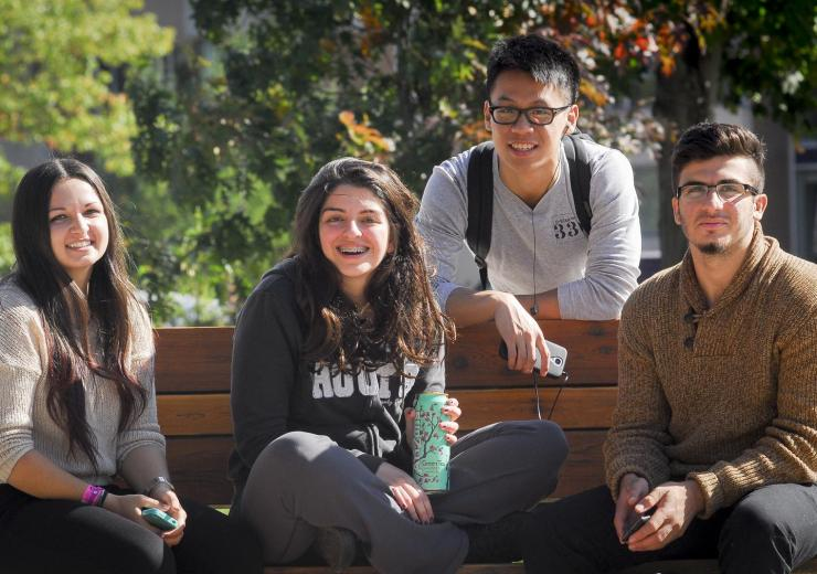 Four students sitting on a bench out side of MW building.