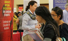 Students speaking to a representative at the Graduate and Professional Schools Fair