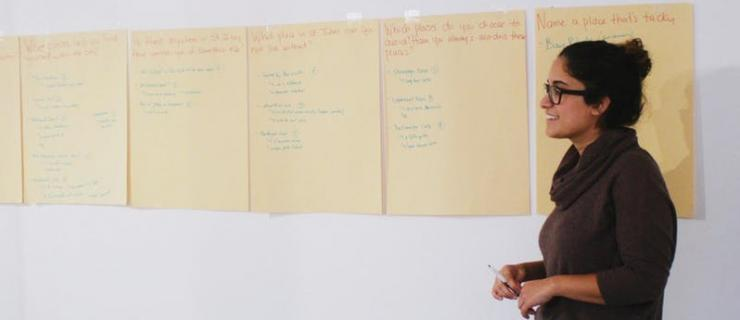 Photo of artist Hiba Abdalla with poster size paper taped on the wall with writing on it.