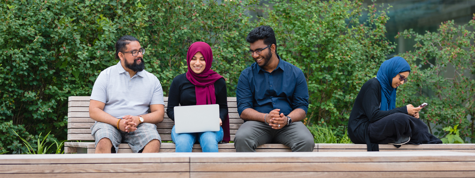 students sitting on bench looking at a laptop