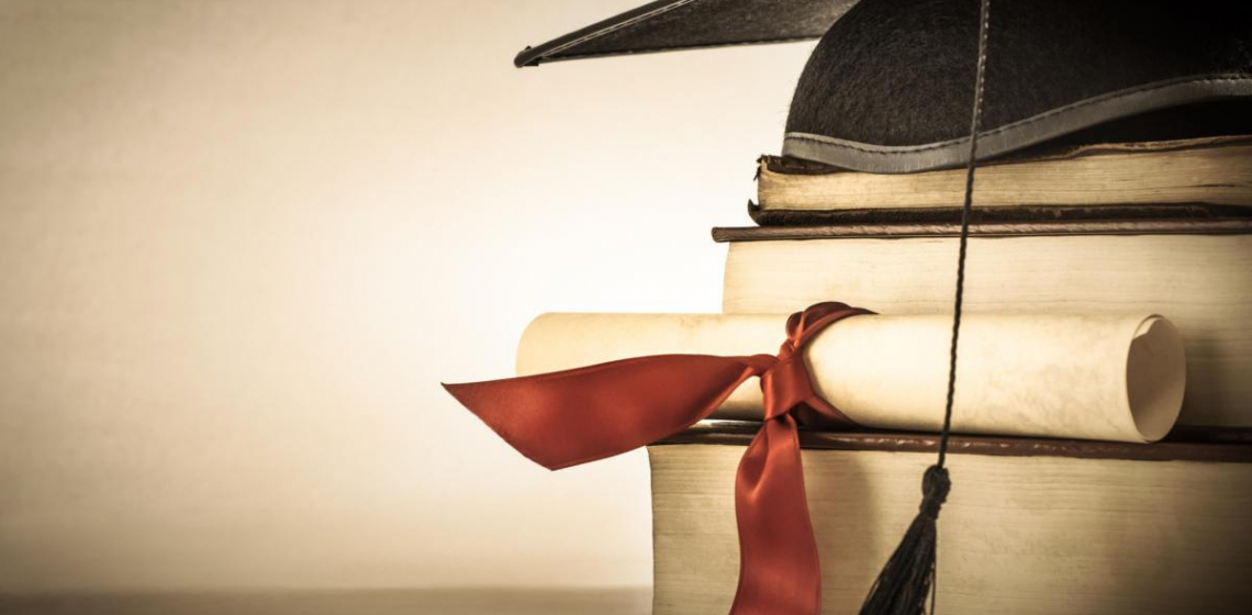 graduation cap on top of books with paper tied with ribbon in front of it
