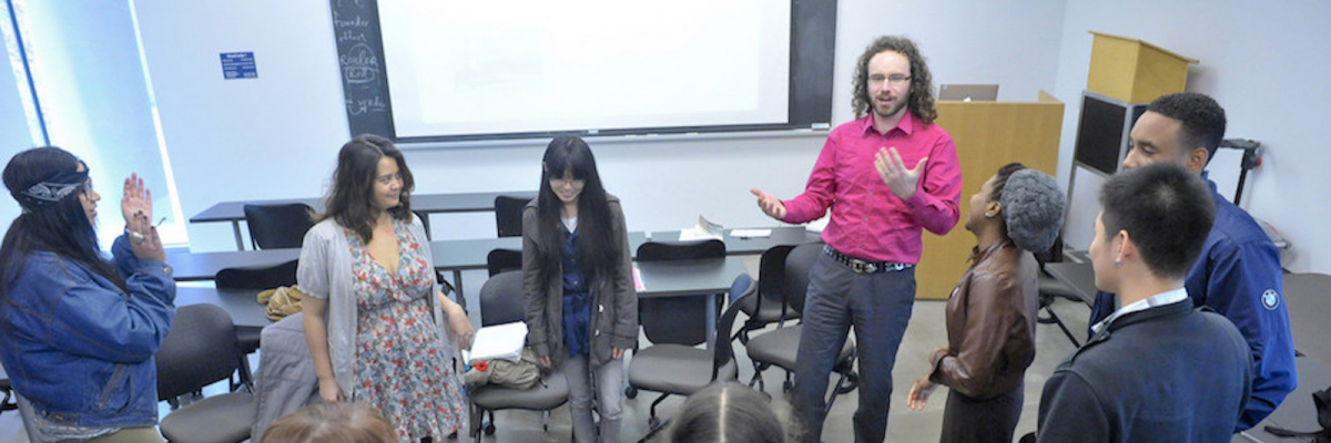 Prof. Daniel Tysdal standing with his students in the classroom