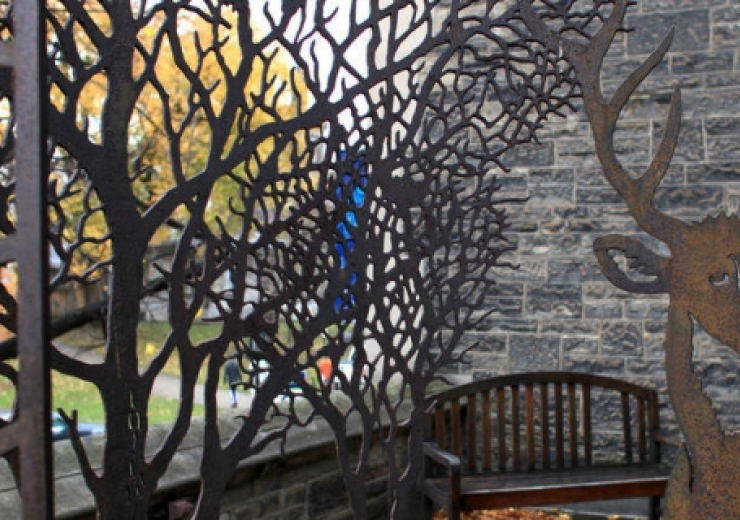 art piece with metal trees and a metal deer set against window with tree in background