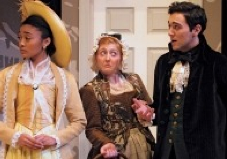 3 people in costumes. from left: woman in yellow dress and yellow hat, woman in green dress, man in suit