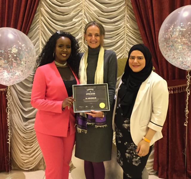 Dr. Bisaillon, a tall white woman, receives an award from two women of color, while standing on a stage wtih balloons and a festive backdrop