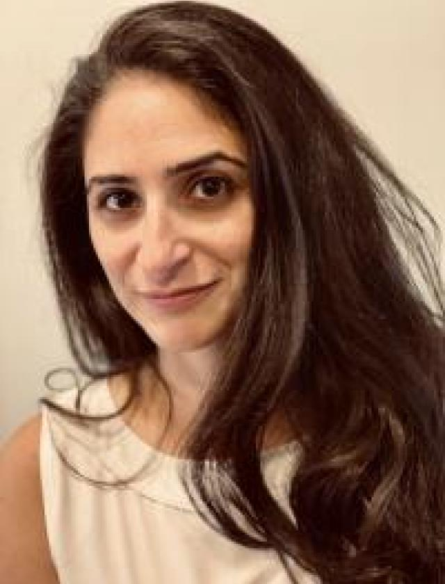 Amira smiles at the camera with her mouth closed. She has long dark hair, dark eyes, olive skin, and is wearing a light colored sleeveless blouse.