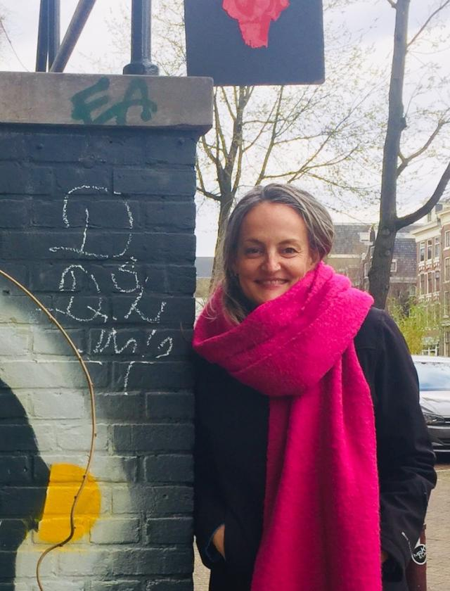 Laura standing next to a dark grey brick wall with graffiti on it wearing an oversized neon pink scarf