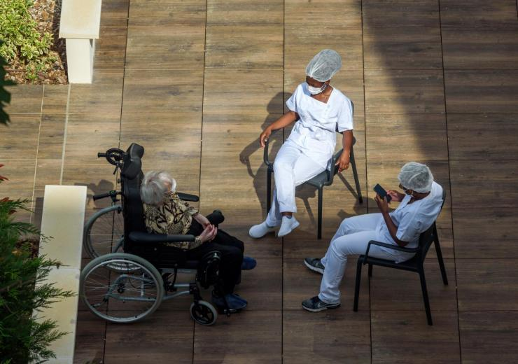 Elderly resident in a courtyard with long term care facility workers