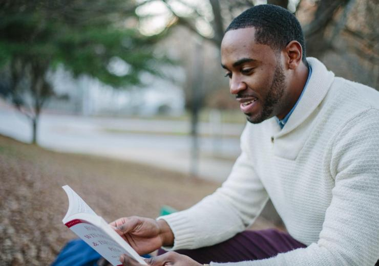 Black man with a close beard and a white sweater reading
