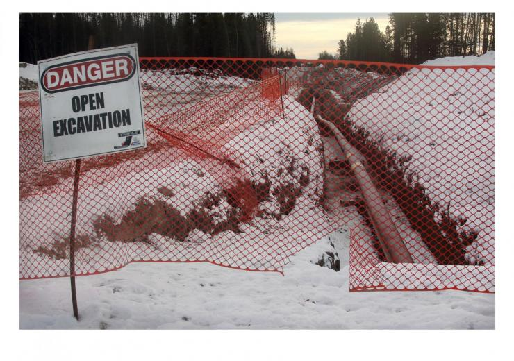 orange construction fence with Open Excavation Sign -- snowy forest setting