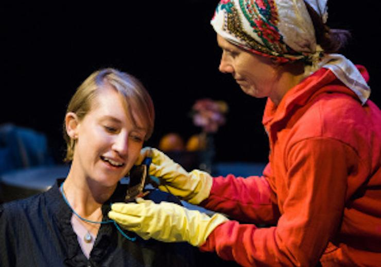 A close up photo: a light-skinned young person, seated, leans their head to the side, and speaks into a flip-phone style cellphone, held for her by a woman in a red sweatshirt wearing a kerchief on her head and yellow cleaning gloves. Both are light brigh