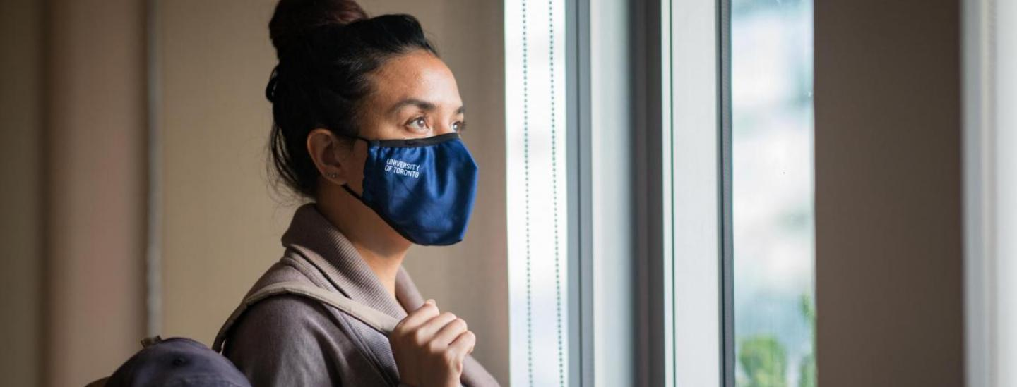 Woman in mask looking out window