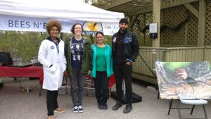 Four people from the Andrade lab stand smiling in front of a tent at the Toronto zoo at an outreach activity.