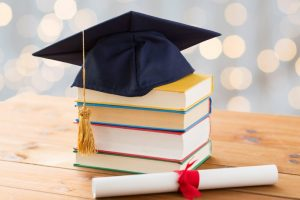 Mortarboard with books and diploma