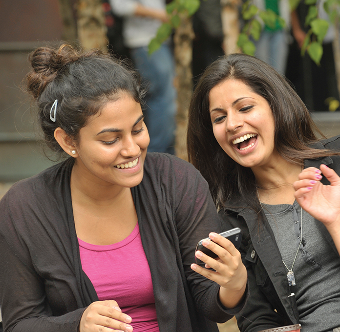 Two UTSC students looking at a phone and laughing