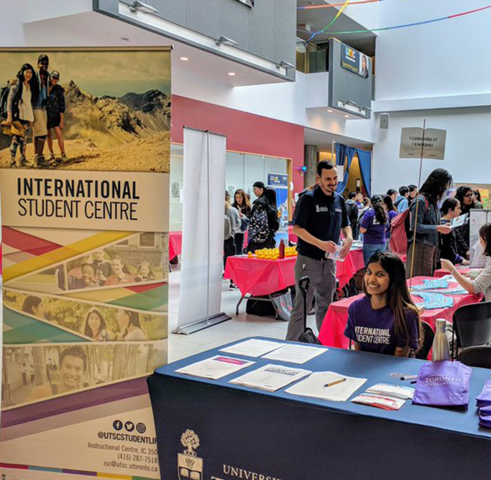 UTSC student greeting guests at international student event