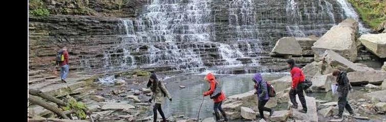 Students walking arcoss a river with waterfalls in the background