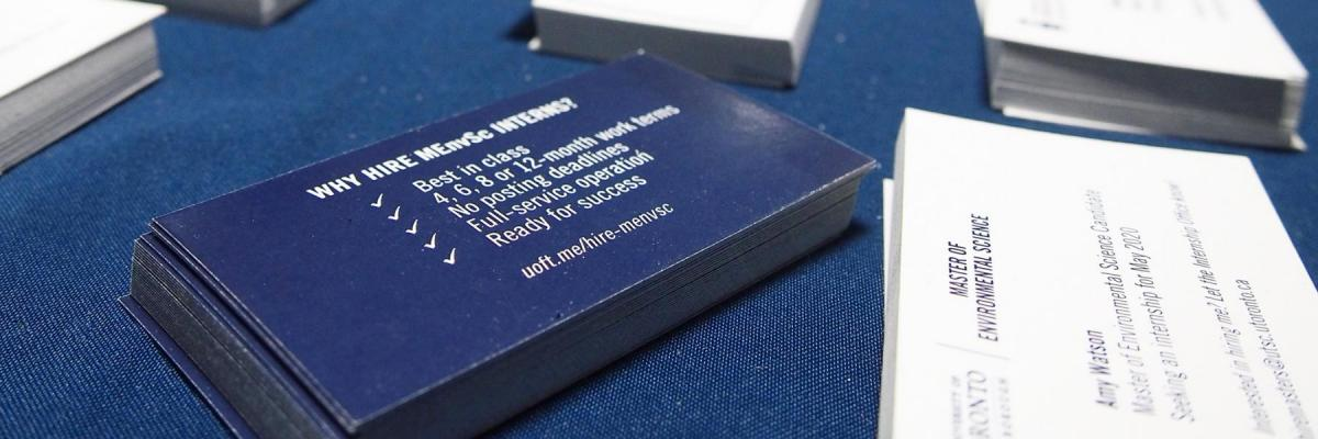 Student business cards laid on a blue table