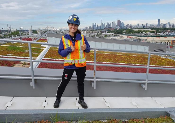 Student intern on top of building with Toronto skyline in background