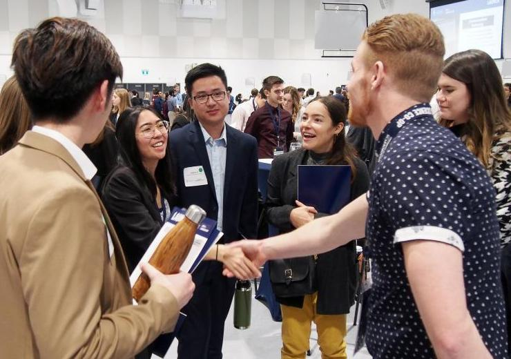 Students shaking hands with an employer at networking event