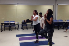 Students performing tree pose at yoga station