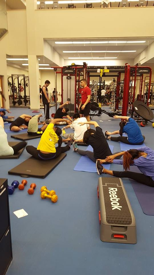 Students on workout mats stretching