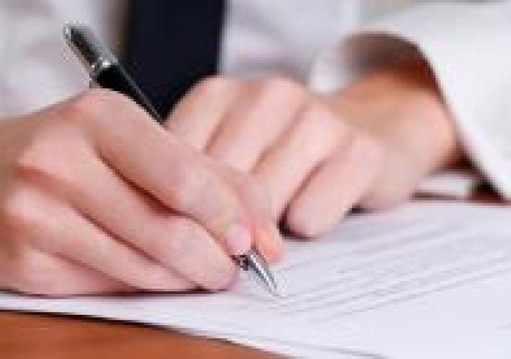 Photo of a document being signed with a pen