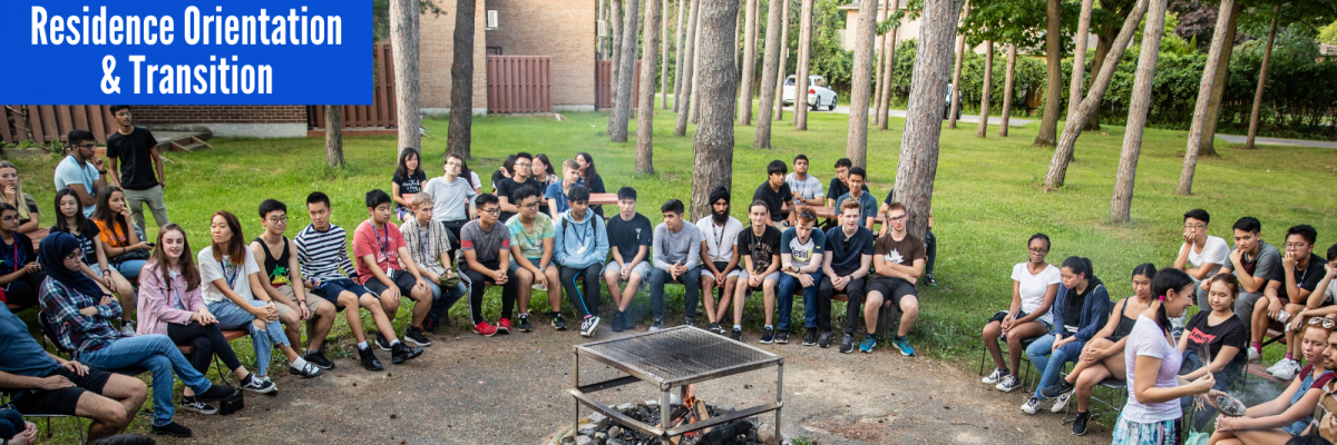 Photograph of residence students sitting around the bonfire pit behind Hickory & Grey Pine halls participating in an Indigenous Learning Circle during Residence Orientation.