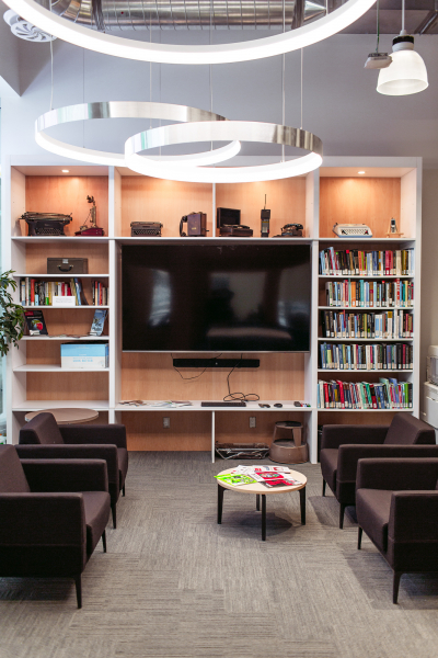 Bookcase with books, large TV and soft seating and tables