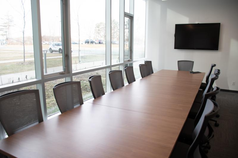 Boardroom with chairs and table, large monitor on wall